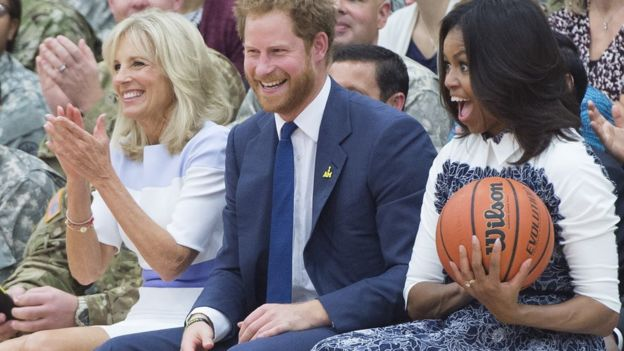 US First Lady Michelle Obama reacts to catching a basketball alongside Britain's Prince Harry and Jill Biden, wife of the US Vice President, as they attend a Wounded Warriors wheelchair basketball game at Fort Belvoir, Virginia, October 28, 2015