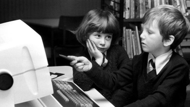 Dos niños frente a una computadora antigua
