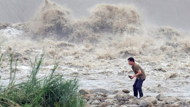 A local resident collects stones from the Xindian river after Typhoon Dujuan passed in the New Taipei City on September 29, 2015.