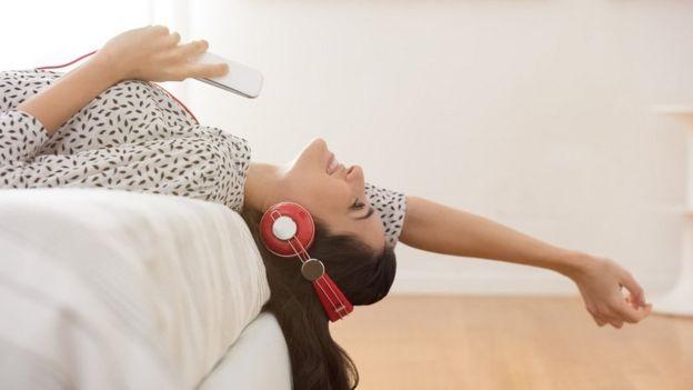 Una joven echada en la cama, disfrutando de música con audífonos