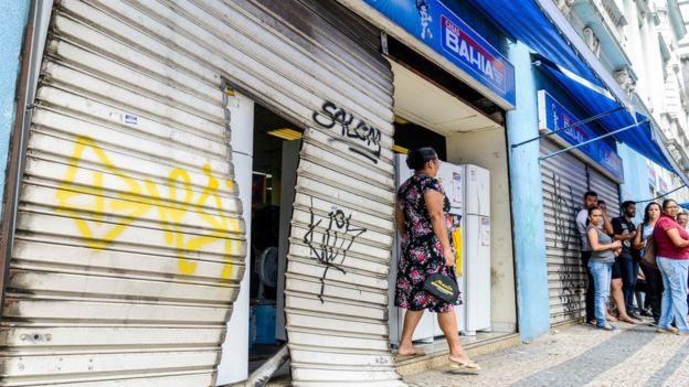 Moradores diante de loja saqueada em Vitória, ES, no dia 6 de fevereiro