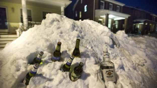 Discarded alcohol bottles sit in the snow in the Friendship Heights neighbourhood of Washington