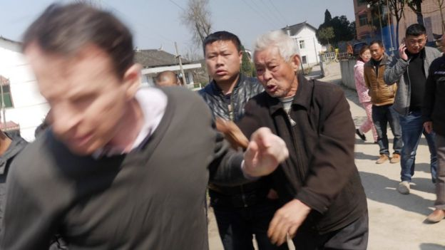 Picture of BBC journalist John Sudworth being forced away from a Chinese village