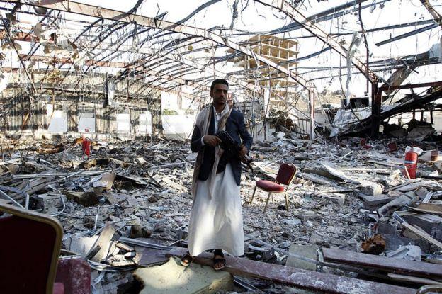 Un hombre yemení en pie y armado en el escenario de un ataque aéreo que tuvo lugar en Yemen el 5 de octubre de 2016, durante un funeral y en el que murieron 140 personas y resultaron heridas 525.