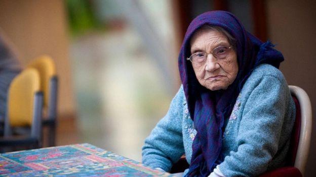 Una señora mayor sentada a una mesa