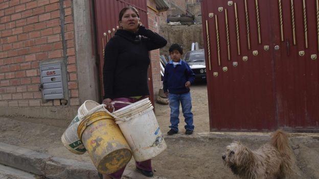Mujer con varios cubos de agua