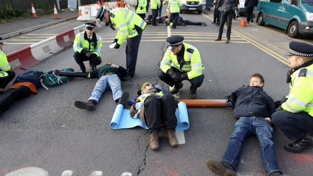 Protesters from campaign group RisingUp! lock themselves together as they block the east ramp at Heathrow Airport