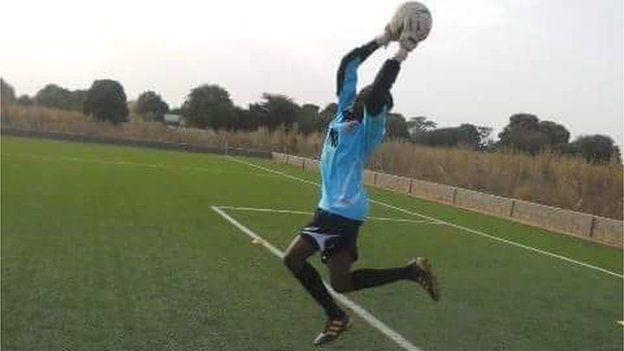 Fatim Jawara throws a ball on a football pitch.