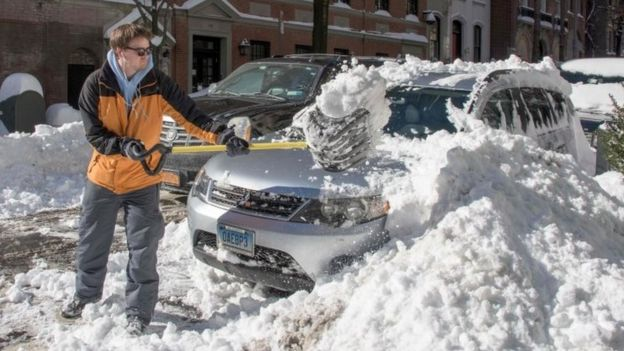 A man clears his car with a shovel near Central Park (24 January 2015)