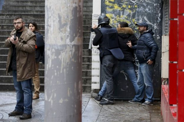 French police check a pedestrian as they secure the area after a man was shot dead at a police station in the 18th district in Paris, France 7 January 2016