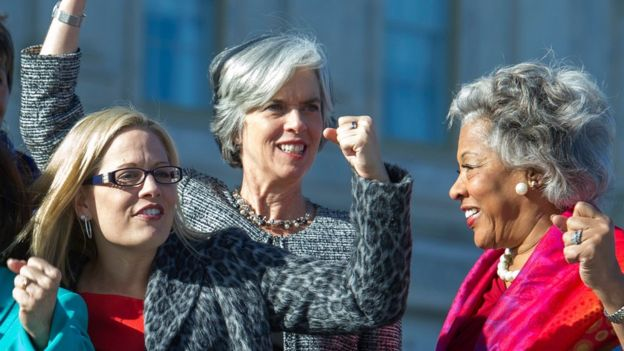 From left, Rep. Kyrsten Sinema, D-Ariz., Rep. Katherine Clark, D-Mass., and Rep. Joyce Beatty, D-Ohio, raise fists during a photo opportunity with the Democratic women of the House, Wednesday, Jan. 4, 2017,