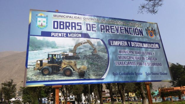 A billboard advertises the measures the local authorities are taking to prevent future disasters
