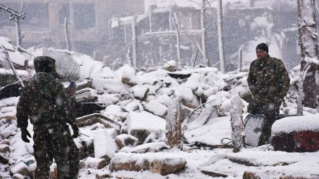 Syrian pro-government fighters stand in the snow in Aleppo (21 December 2016)