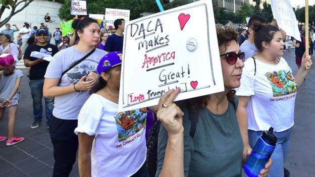 Young immigrants and supporters walk holding signs during a rally in support of Daca in Los Angeles, on September 1, 2017