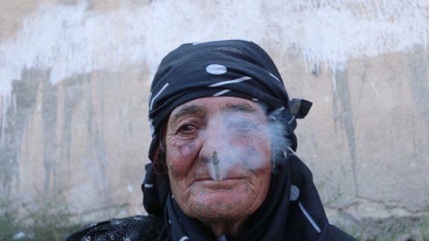 Una mujer fuma en Manbji tras la liberación de la ciudad que había estado bajo control de EI.