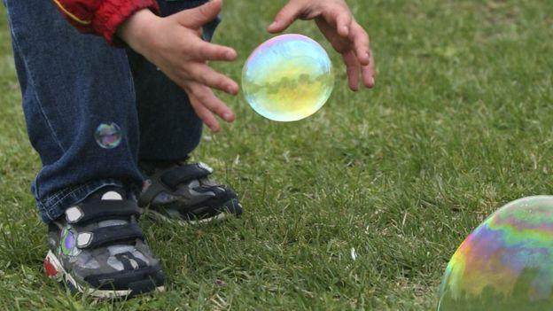 Niño persigue burbujas