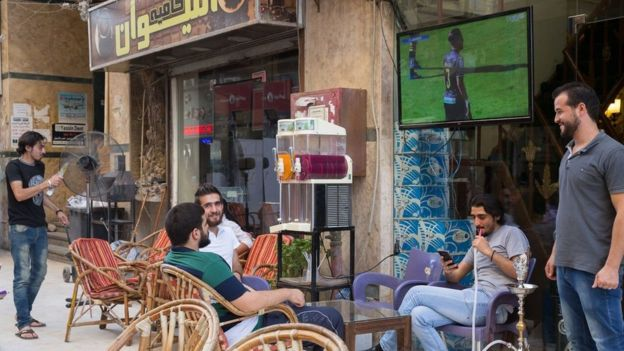 Men socialise and watch football in the area that has been recently named Little Damascus due to the high number of Syrians opening businesses there