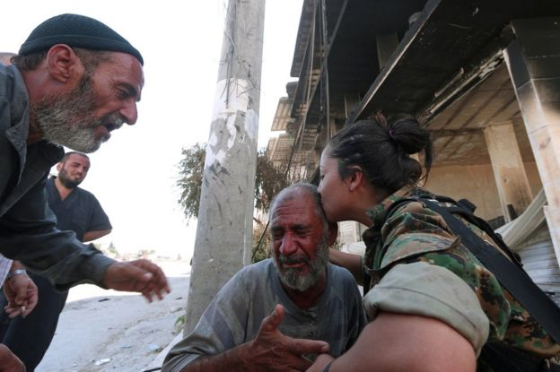 A fighter comforts civilians who were evacuated an Islamic State-controlled neighborhood of Manbij, Syria, 12 August