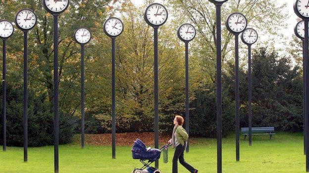 Una mujer camina con un cochecito de bebé en un parque con una instalación de muchos relojes