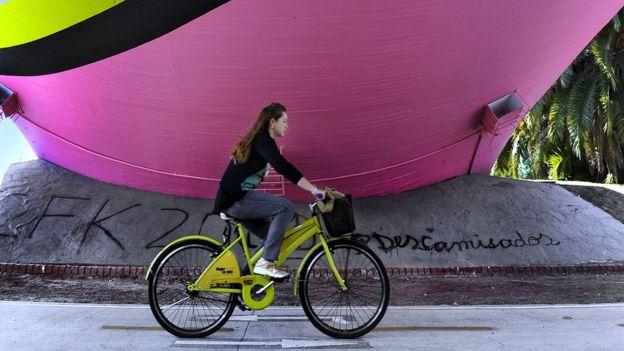 Una mujer monta una ecobici en Buenos Aires.
