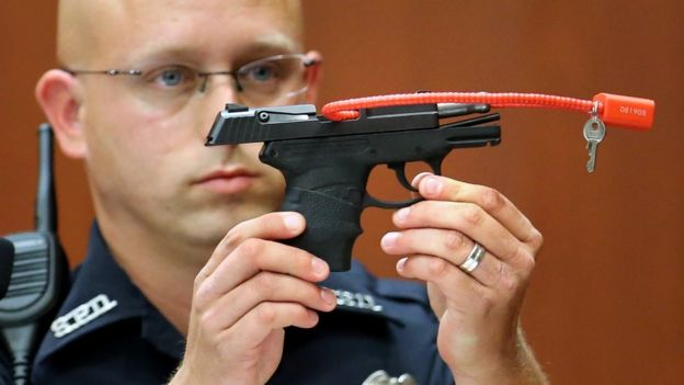 Sanford police officer Timothy Smith holds up the gun that was used to kill Trayvon Martin - June 2013