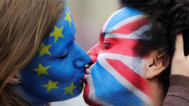 Two activists with the EU flag and Union Jack painted on their faces kiss each other in front of Brandenburg Gate to protest against the British exit from the European Union, in Berlin, Germany (June 19, 2016)
