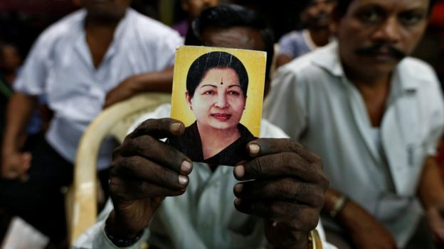 A supporter of Tamil Nadu Chief Minister Jayalalitha Jayaraman holds her photo at the AIADMK party office in Mumbai, India, December 5