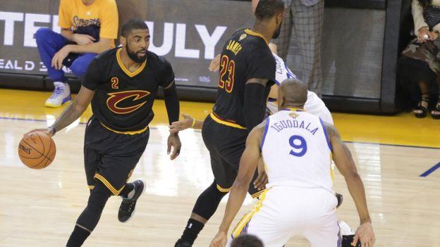 Kyrie Irving (2) mueve la pelota mientras LeBron James (23) de los Cavaliers bloquea a Stephen Curry (30) de los Warriors en la primera mitad en el séptimo partido de las Finales de la NBA.