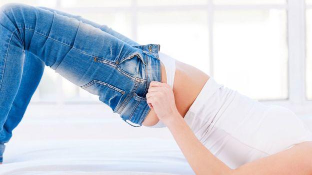 Mujer en la cama intentando subirse un jean