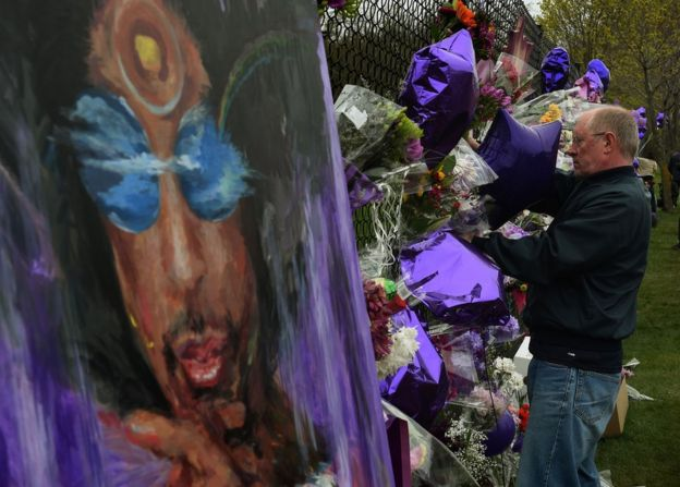 A Prince fans attaches flowers to a memorial wall as he pays his respects outside the Paisley Park residential in Minneapolis, Minnesota, 22 April