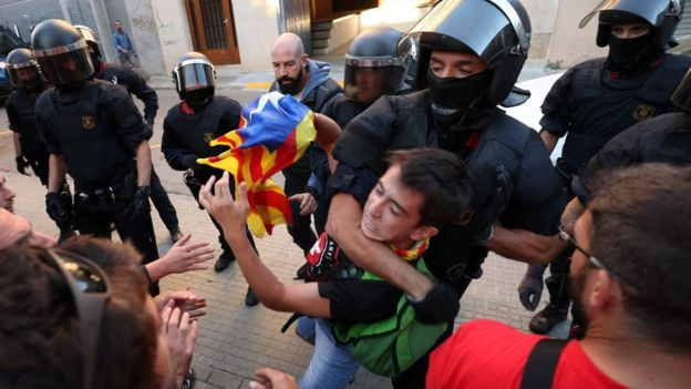 Police remove a protester outside Unipost office in Terrassa on 19 Sept