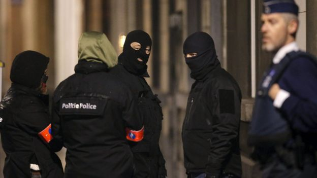 Masked police secure entrance to building in Schaerbeek during police operations in Brussels. 25 March 2016