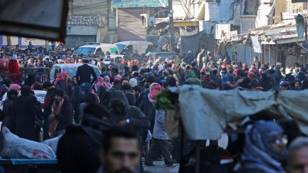People gather in the rebel-held al-Sukkari district to be evacuated, 15 Dec