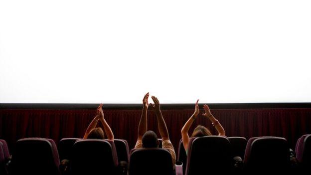 personas aplaudiendo en el cine
