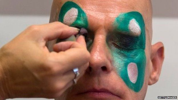 A man has his make-up applied at the London School of Samba