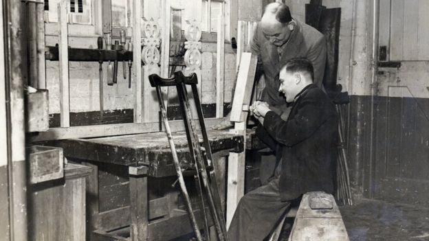 A man with a crutch at his work station with a man watching 1930s