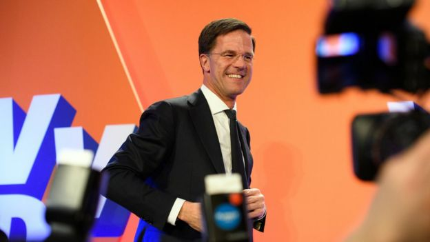 Centre-right leader Mark Rutte smiling on a stage in front of orange backdrop