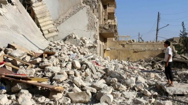 A young Syrian looks at the rubble of a collapsed building as rescuers look for victims after a reported air strike on the Sakhur area of northern Aleppo 19/07/2016