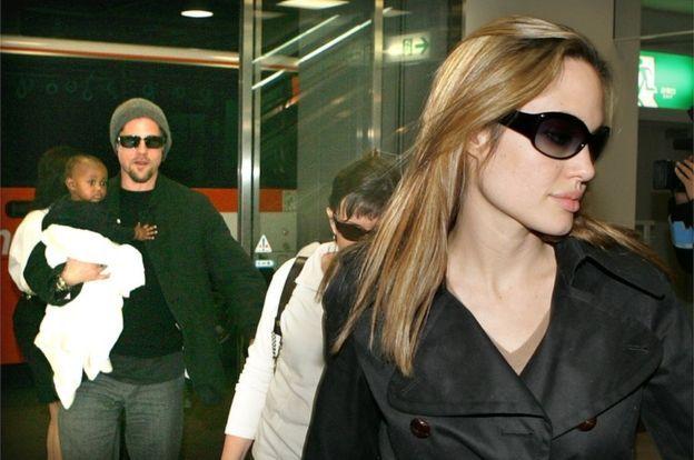 يُشاهد بيت وهو يحمل زهارا بعدما وصل الزوجان إلى مطار طوكيو في عام 2005