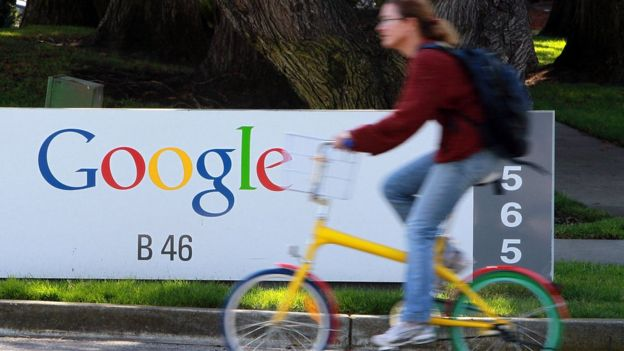Cyclist rides past Google sign in Mountain View
