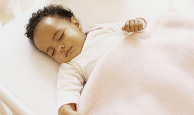 Baby asleep in pink linen