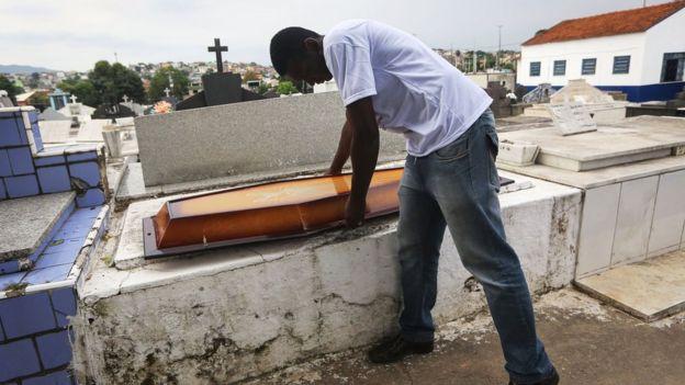 Leonardo Martins da Silva ao pegar a tampa para feixar caixão do filho