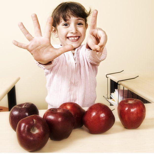 Menina mostrando nas mãos quantas maçãs tem