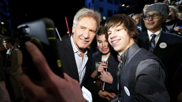 Harrison Ford poses with a fan at the Star Wars premiere