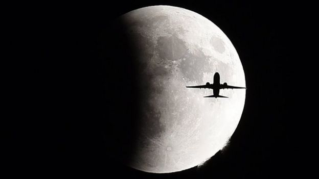 A plane flies in front of the supermoon over Geneva, Switzerland