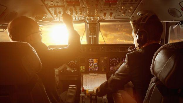 Piloto y copiloto en un avión durante la puesta de sol.