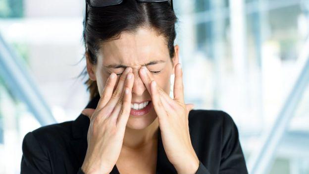 Mujer restregándose los ojos