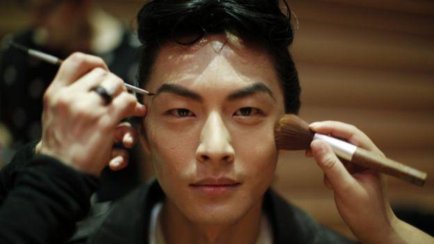 Un hombre es maquillado.