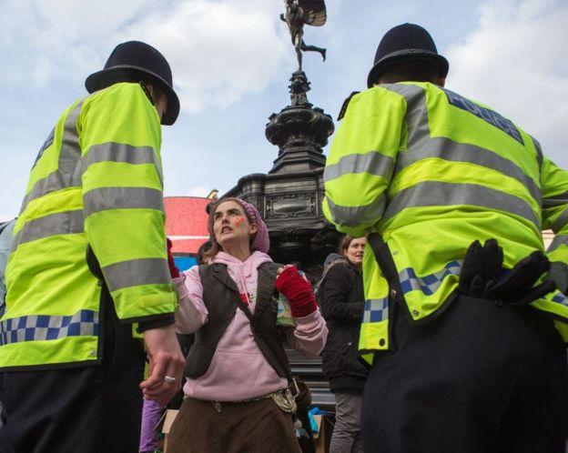 Policías frente a una manifestante en Trafalgar Square, Londres.