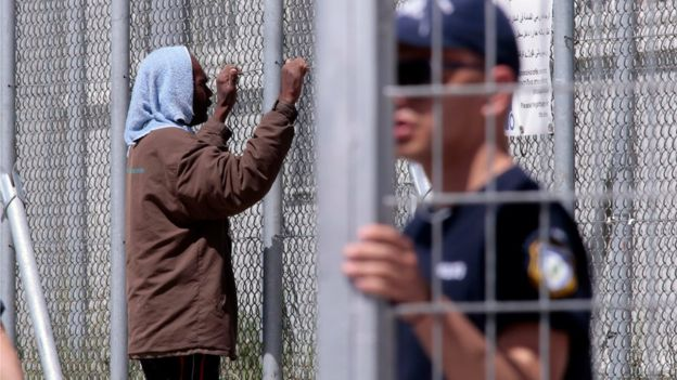 A man looks through a gate at the Moria refugee camp where asylum-seekers are held at the complex on April 15, 2016 in Mytilene on Lesbos